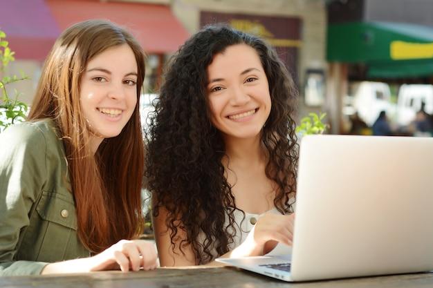 Amigos femeninos que estudian con un ordenador portátil en una cafetería.