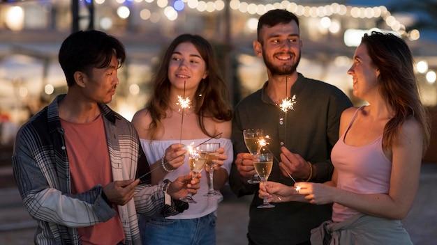 Amigos de fiesta con fuegos artificiales por la noche