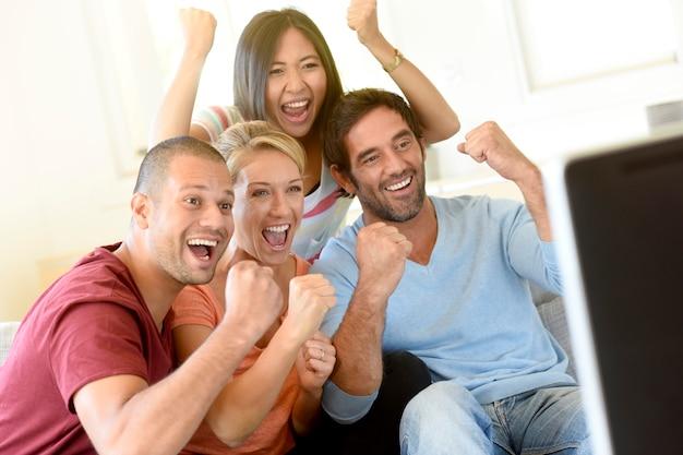 Amigos en frente de la televisión viendo el juego