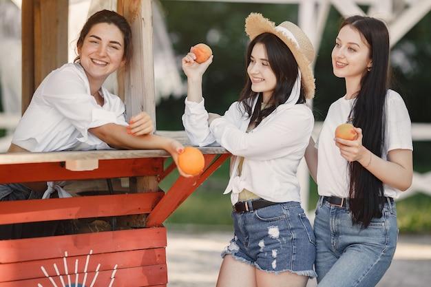 Amigos con frutas. chica con sombrero. mujer con camiseta blanca.