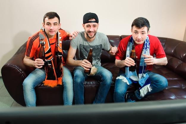 Amigos de fútbol fanáticos que miran fútbol, fútbol en casa