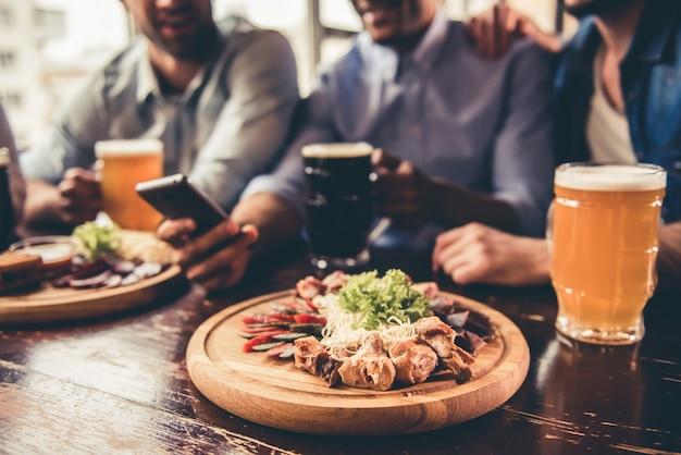 Amigos guapos están bebiendo cerveza, utilizando teléfonos inteligentes.