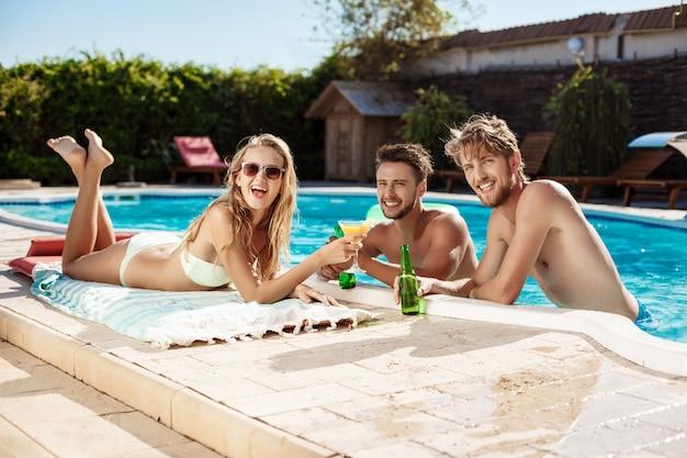 Amigos hablando, sonriendo, bebiendo cócteles, descansando, relajándose cerca de la piscina