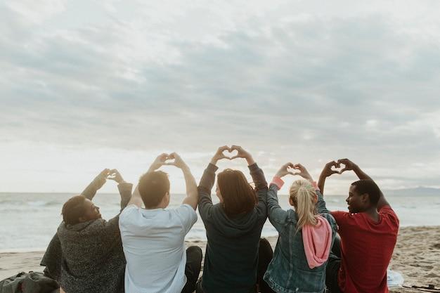 Amigos haciendo el amor con las manos del corazón en la playa