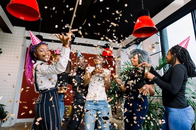 Amigos haciendo una gran fiesta en la noche. seis personas africanas lanzando confeti y bebiendo champán