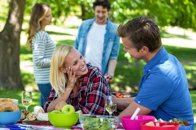 Amigos haciendo un picnic con vino y barbacoa.