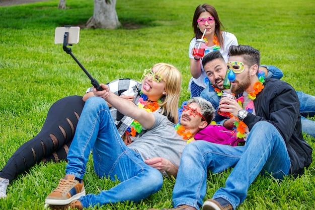 Amigos haciendo selfie en el festival de verano con máscaras y collares