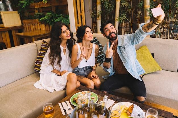 Amigos haciendo selfie en restaurante