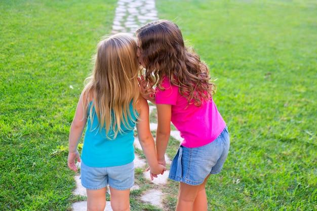 Amigos hermana chicas susurrando secreto en el oído en el jardín
