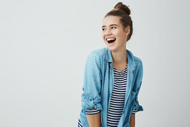 Amigos hilarantes alegran la vida. foto de estudio de una novia linda, emotiva y positiva con un peinado de moño doblado hacia la derecha mientras se aparta y se ríe, está de buen humor, sale con su novio
