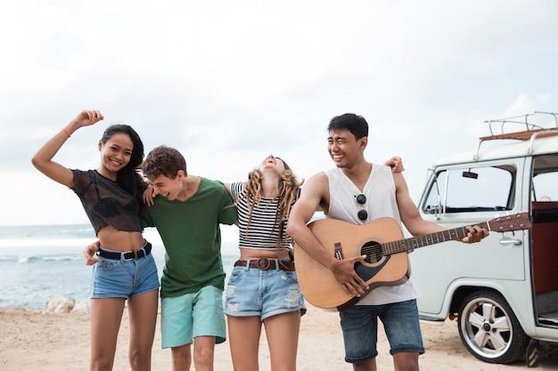 Amigos hipster disfrutando en la playa