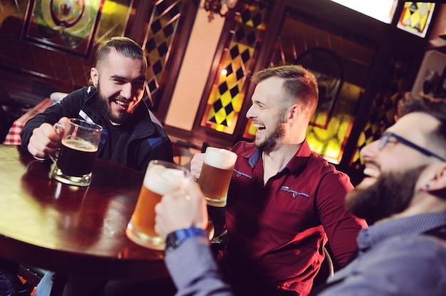 Amigos - hombres jóvenes y lindos beben cerveza en un bar, con gafas, sonriendo, riendo y hablando.