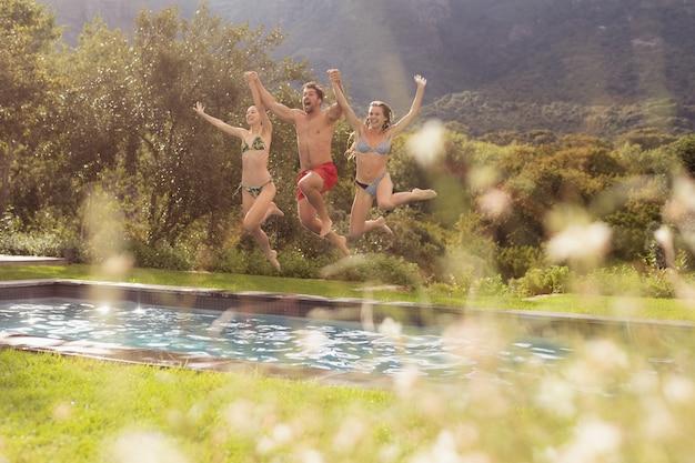 Amigos hombres y mujeres saltando en la piscina en el patio trasero