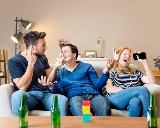 Amigos hombres riéndose de mujer por cantar con auriculares en