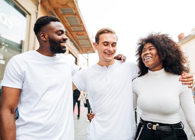 Amigos interculturales abrazándose y caminando juntos