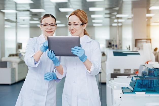 Amigos íntimos. trabajadores médicos femeninos sonrientes de pie en primer plano sosteniendo la tableta mientras miran su pantalla