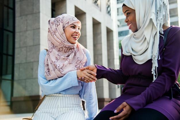 Amigos islámicos apretón de manos y sonriendo