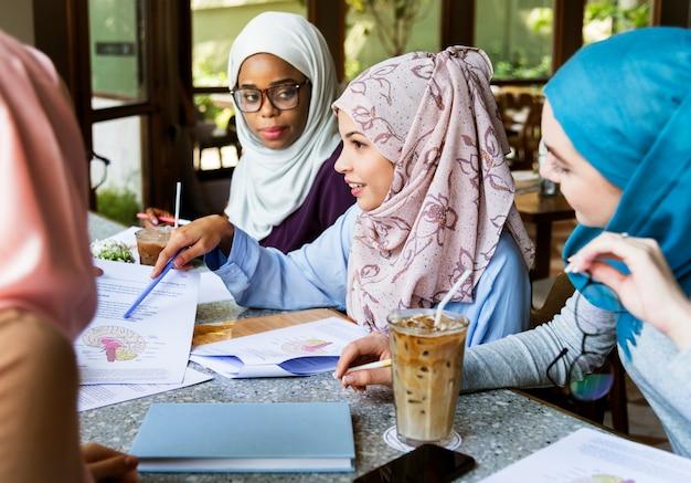 Amigos islámicos discutiendo y leyendo libros juntos
