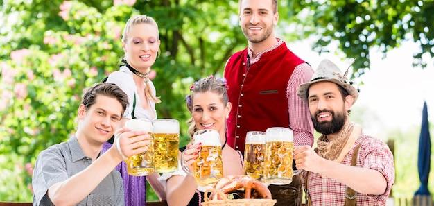 Amigos en el jardín de la cerveza de baviera bebiendo en verano