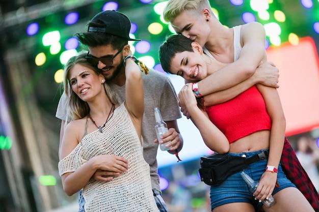 Amigos jóvenes felices divirtiéndose en el festival de música