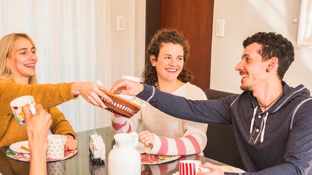 Amigos jovenes felices que se sientan en la mesa de comedor que disfruta del desayuno