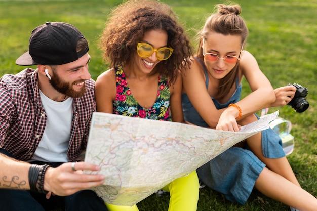 Amigos jóvenes felices sentados en el parque, mirando en el mapa