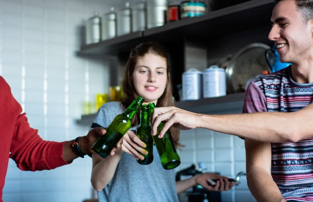 Amigos jovenes que se divierten con las botellas en casa.
