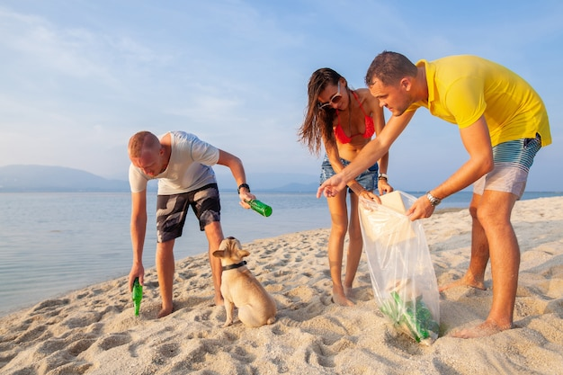 Amigos jóvenes recogiendo basura y basura en una playa tropical salvando el planeta y la ecología en indonesia, tailandia y filipinas