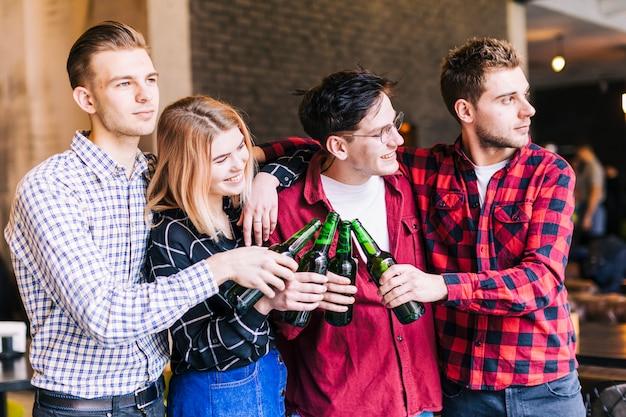Amigos jóvenes tintineando con botellas de cerveza en el bar