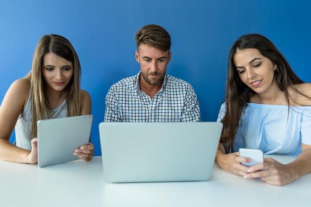 Amigos jóvenes trabajando con dispositivos