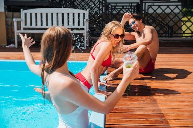 Amigos jugando con el agua en la piscina.