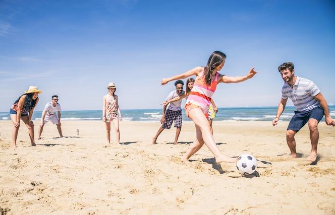 Amigos jugando al fútbol en la playa