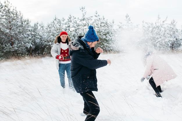 Amigos jugando bolas de nieve en el bosque de invierno