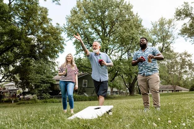 Amigos jugando cornhole en una fiesta de verano en el parque