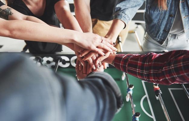 Los amigos juntos juegan juegos de mesa, futbolín, se divierten el tiempo libre.