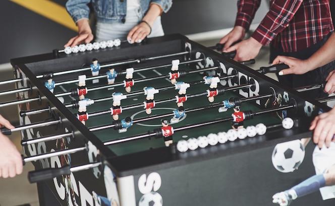 Amigos juntos juegan juegos de mesa, futbolín