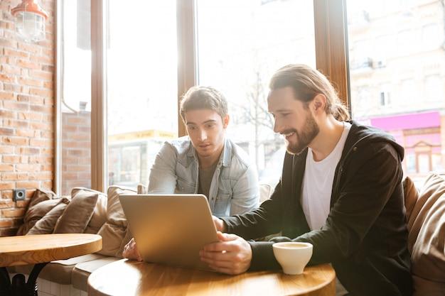 Amigos con laptop en cafe