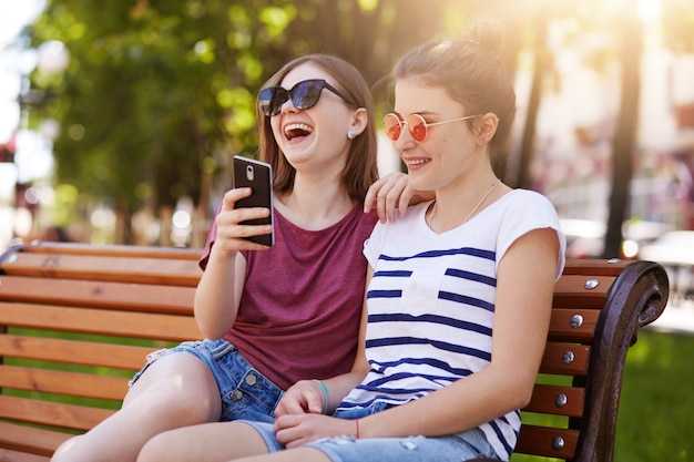 Los amigos leales y felices se sienten bien cerca el uno del otro en el parque.