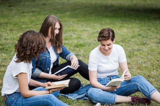 Amigos leyendo juntos sobre hierba