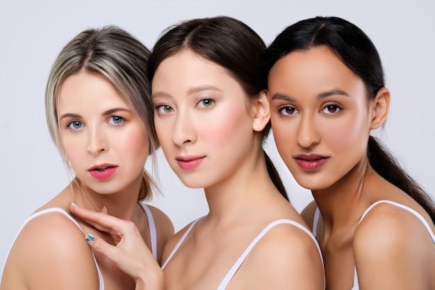 Amigos lindos: chicas asiáticas, caucásicas y africanas que se inclinan entre sí