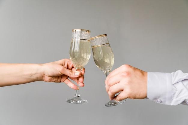 Amigos manos tintinean copas de champán sobre fondo gris