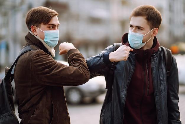 Amigos en máscara médica protectora en su rostro saludan a sus codos