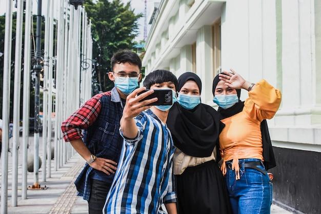 Amigos con máscara protectora de seguridad divirtiéndose tomando selfies durante la pandemia del virus corona