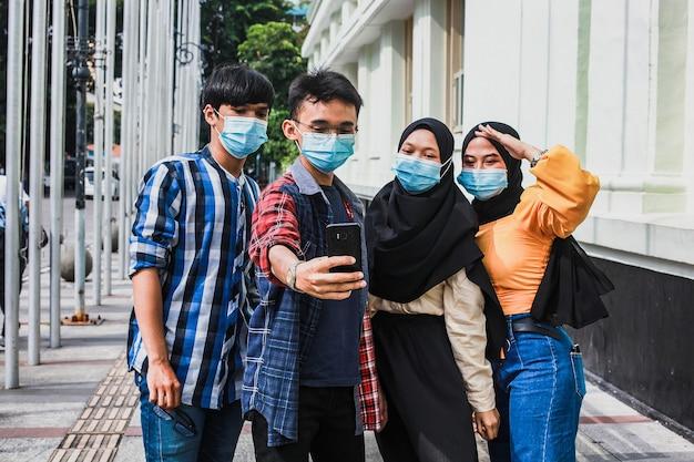 Amigos con máscara protectora de seguridad que se divierten tomando selfies durante la pandemia del virus corona