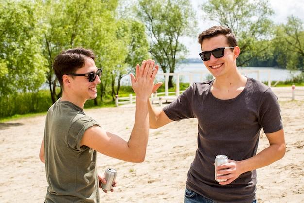 Amigos masculinos alegres dando alta cinco