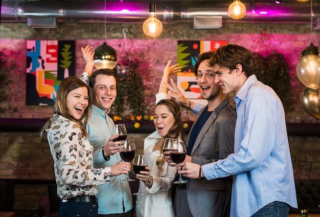 Amigos masculinos y femeninos disfrutando de bebidas mientras bailan en el bar