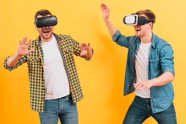Amigos masculinos jovenes felices que llevan los vidrios de la realidad virtual que se ríen contra fondo amarillo
