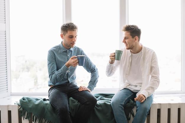 Amigos masculinos jovenes que desayunan por la mañana en casa