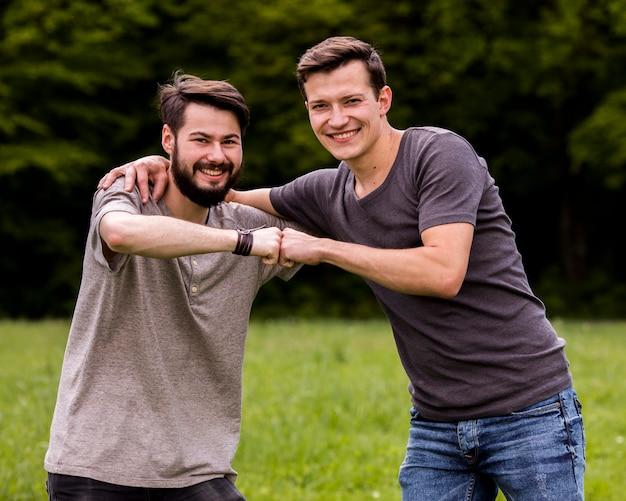 Amigos masculinos que abrazan en el parque