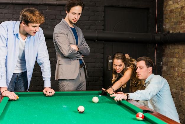 Amigos masculinos que miran a la mujer que juega el billar en club